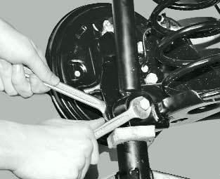 Отворачивание нижнего болта амортизатора Форд Фокус 1